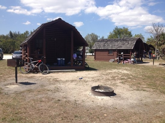 each cabin has a bar b q picnic table and a fire pit picture of Oleta River State Park Cabins