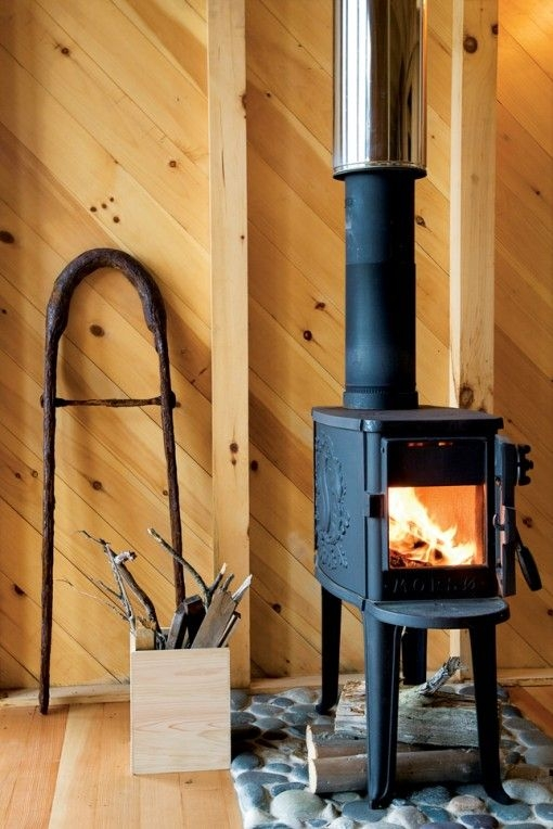 freestanding woodstove on stone platform small sustainable cabin Small Wood Burning Stoves For Cabins